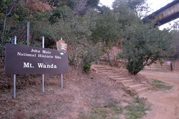The Mt. Wanda trail entrance showing sign, steps, and overhead train trestle